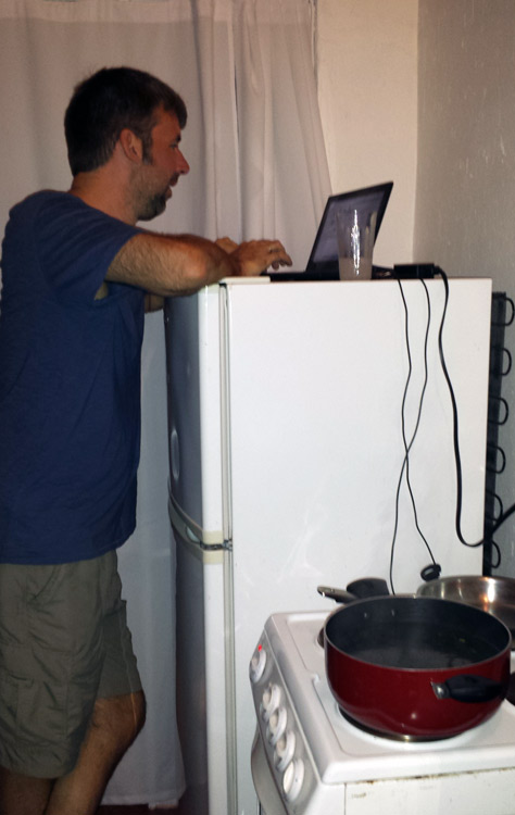 Image of Mark using refrigerator as a desk