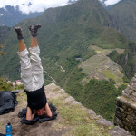 Julie doing a headstand at the top of Huayan Picchu. You can see the ruins of Machu Picchu below.